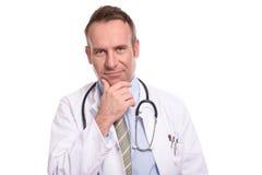 Fundersam doktor som ser kameran fotografering för bildbyråer