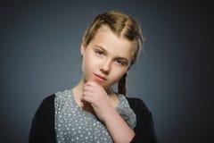 Fundersam flicka för Closeup med handen på huvudet som isoleras på grå färger arkivfoton