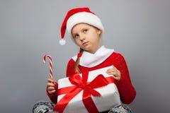 Fundersam flicka med en gåva för nytt år Royaltyfri Foto