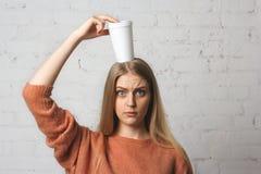 Fundersam flicka med en kopp kaffe på hans huvud Royaltyfri Foto