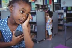 Fundersam flicka som ser bort, medan rymma mobiltelefonen Royaltyfri Bild