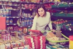 Fundersam flickakund som söker efter smakliga sötsaker i supermarket Arkivbild
