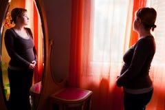 Fundersam gravid kvinna Fotografering för Bildbyråer