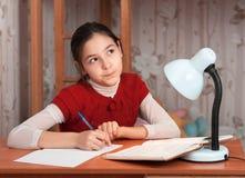 Fundersam flicka som gör läxa på bordlägga Royaltyfria Bilder