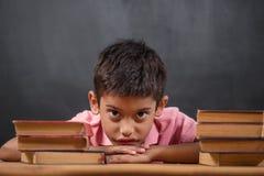 Fundersam gullig klyftig pojke med boken på tabellen Första gång till skolan tillbaka skola till Royaltyfri Foto