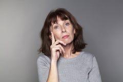 Fundersam härlig 50-talkvinna som ser olycklig Arkivfoto