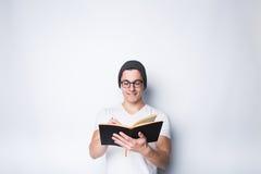 Fundersam hållande anteckningsbok för manlig student och se upp isolerat på en vit bakgrund Arkivbild