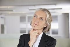 Fundersam hög affärskvinna som i regeringsställning ser upp Royaltyfri Bild