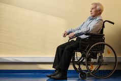 Fundersam hög man i rullstol Arkivbilder