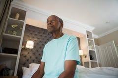 Fundersam hög man som ser bort, medan sitta hemma royaltyfri foto