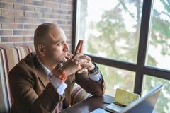 Fundersam indisk affärsman som sitter nära fönster och utanför ser fotografering för bildbyråer
