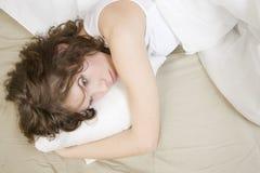 fundersam kvinna för attraktiv brunettkrullning Arkivbild