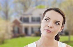 Fundersam kvinna för blandat lopp framme av huset Arkivfoto