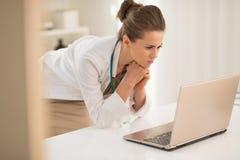 Fundersam kvinna för medicinsk doktor som ser i bärbar dator Royaltyfria Bilder