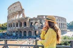 Fundersam kvinna framme av colosseumen i rome Arkivfoto