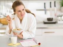 Fundersam kvinna i badrock som äter frukosten Royaltyfri Bild