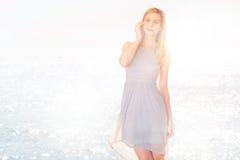 Fundersam kvinna i den tillfälliga klänningen som ser bort mot havet Arkivfoto