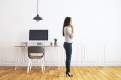 Fundersam kvinna i rum med arbetsplatsen Fotografering för Bildbyråer