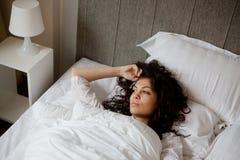 Fundersam kvinna i säng Royaltyfria Foton