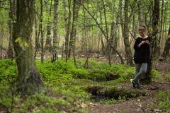 Fundersam kvinna i skogen Arkivbild