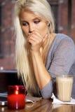 Fundersam kvinna med bärbar dator på cafen Arkivfoto