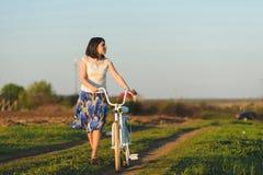 Fundersam kvinna med cykeln Royaltyfri Foto