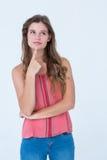 Fundersam kvinna med fingret på hakan Fotografering för Bildbyråer