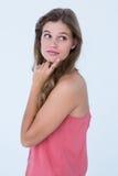 Fundersam kvinna med fingret på hakan Arkivfoto