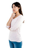 Fundersam kvinna med handen på kind Arkivbild