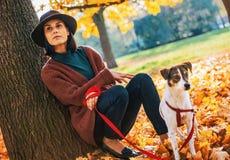 Fundersam kvinna med hunden utomhus i höst Royaltyfria Foton