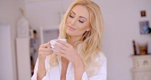 Fundersam kvinna med kaffe som stänger henne ögon Arkivbilder
