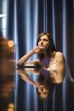 Fundersam kvinna med tekoppen i Caf-ホ Arkivfoton