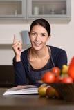Fundersam kvinna på köket med receptboken Royaltyfri Fotografi