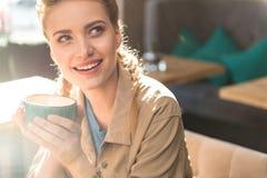 Fundersam kvinna som dricker koppen kaffe arkivfoto