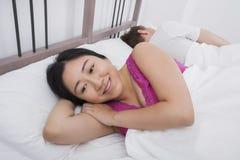 Fundersam kvinna som ler medan man som sover i säng Royaltyfri Fotografi