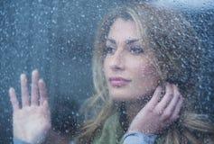 Fundersam kvinna som ser till och med fönster med regndroppar Arkivbild