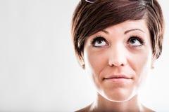 Fundersam kvinna som ser upp in i luften Arkivfoto