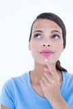Fundersam kvinna som ser upp med fingret på hakan Arkivfoton