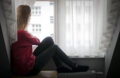 Fundersam kvinna som ut ser fönstret Arkivfoton
