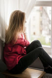 Fundersam kvinna som ut ser fönstret Arkivfoto