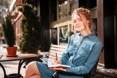 Fundersam kvinnareadngbok och drömma på beanchen utomhus arkivfoto