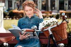 Fundersam kvinnareadngbok och drömma på beanchen utomhus royaltyfri bild