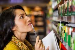 Fundersam kvinnashopping för livsmedelsbutik royaltyfria bilder