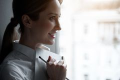 Fundersam kvinnlig hållande tidsbeställningsbok i arm arkivbild