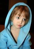 Fundersam liten flicka i blå badrock med huven arkivfoton