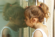Fundersam liten flicka som ser till och med fönstret Royaltyfri Bild