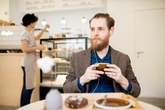 Fundersam man i hörlurar som kopplar av i coffee shop royaltyfria bilder