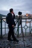 Fundersam man i svarta kläder med kameran och tripoden som väntar vid en flod arkivbilder