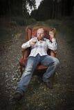Fundersam man som dricker Cognac i en tappningstol Royaltyfri Bild