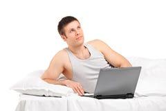 Fundersam man som ligger och fungerar på en bärbar dator Royaltyfri Fotografi
